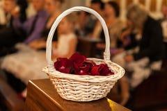 Drewniany kosz z czerwieni róży płatkami obrazy stock