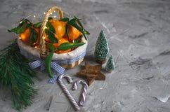 Drewniany Koszykowy Mandarine z liśćmi i światłami, Tangerine pomarańcze na szarość stołu tła nowego roku Bożenarodzeniowych wyst obrazy royalty free