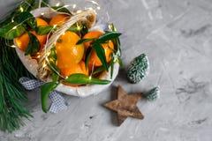 Drewniany Koszykowy Mandarine z liśćmi i światłami, Tangerine pomarańcze na szarość stołu tła nowego roku Bożenarodzeniowych wyst fotografia stock
