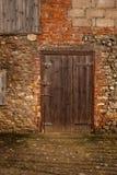 Drewniany kraszony stajni drzwi w pomarańczowej ścianie z cegieł a za budynku na gospodarstwie rolnym obraz stock