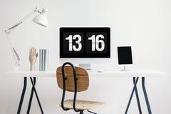 Drewniany krzesło przy biurkiem z białą lampą i komputerem stacjonarnym w prostym ministerstwa spraw wewnętrznych wnętrzu Istna f zdjęcie royalty free