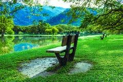 Drewniany krzesło przy jezioro ogródem Obrazy Stock