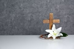 Drewniany krzyż, korona ciernie i okwitnięcie leluja na stole przeciw koloru tłu, zdjęcie stock