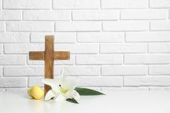 Drewniany krzyż, Wielkanocni jajka i okwitnięcie leluja na stole przeciw ścianie z cegieł, obrazy stock