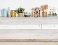 Drewniany kuchenny stół nad zamazaną meblarską półką z karmowymi składnikami Fotografia Royalty Free