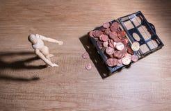 Drewniany lala mężczyzna z jego savings, złocista moneta Wszystko komponowali z centem, tajlandzkim bahtem i Juan tajlandzkiego b Zdjęcie Stock