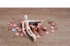 Drewniany lala mężczyzna z jego savings, złocista moneta Wszystko komponowali z centem, tajlandzkim bahtem i Juan tajlandzkiego b Fotografia Stock