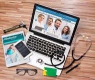 Drewniany lekarki biurko w wysokiej definici z laptopem, pastylką i mo, fotografia stock
