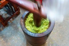 Drewniany młoteczkowy upadanie na zielonych ryż dla gotować Tajlandzkiego cukierki cere zdjęcia stock