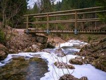 Drewniany mały most nad zamarzniętą rzeką zdjęcie royalty free