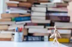 Drewniany manikin spacer w kierunku książek w tle fotografia royalty free