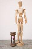 Drewniany mannequin i hourglass wydaje czas Zdjęcie Royalty Free