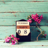 Drewniany Marzec 8 kalendarzowy, obok purpurowych kwiatów na starym błękitnym wieśniaka stole Selekcyjna ostrość Zdjęcie Stock