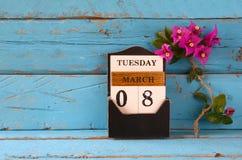 Drewniany Marzec 8 kalendarzowy, obok purpurowych kwiatów na starym błękitnym wieśniaka stole Selekcyjna ostrość Zdjęcie Royalty Free