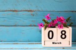 Drewniany Marzec 8 kalendarzowy, obok purpurowych kwiatów na starym błękitnym wieśniaka stole Selekcyjna ostrość Rocznik filtrują Obrazy Stock