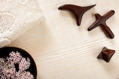 Drewniany masaż wtyka, watowaty Terry ręcznik, puchar z kwiatami na światło malującym drewnianym tle fotografia royalty free