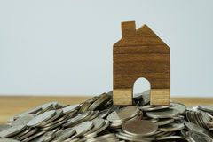 Drewniany miniatura dom na górze sterty monety jako pieniężny sav Obrazy Royalty Free