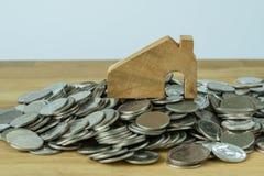 Drewniany miniatura dom na górze sterty monety jako pieniężny sav Zdjęcie Royalty Free
