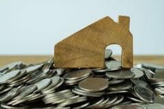 Drewniany miniatura dom na górze sterty monety jako pieniężny sav Zdjęcie Stock