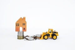 Drewniany miniatura dom na monety stercie z frontowymi ładowacz ciężarówki chodzenia monetami Zdjęcie Stock