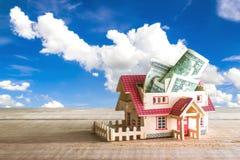 drewniany modela dom z pieniądze inside na drewno stole z odbitkowym zdrojem Fotografia Stock