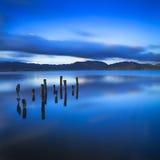 Drewniany molo lub jetty zostajemy na błękitnym jeziornym zmierzchu i nieba refle Obrazy Stock