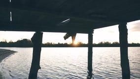 Drewniany molo na rzece w położenia słońcu, dziewczyny ` s iść na piechotę zbiory