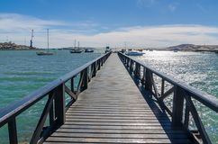Drewniany molo prowadzi out w zatokę na słonecznym dniu z wiele łodziami, Luderitz, Namibia, afryka poludniowa Zdjęcie Stock