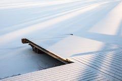 Drewniany molo zakrywający z śniegiem, zimy jezioro Obraz Royalty Free