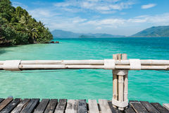 Drewniany most z bambusa ogrodzeniem na niebieskiego nieba i morza tle Zdjęcie Stock