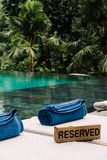 Drewniany nameplate Rezerwujący sunbeds zbliża basenu obraz stock