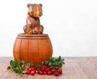 Drewniany niedźwiedź na małej baryłce z wiązką lingonberries Obraz Stock