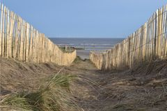 Drewniany ogrodzenie na diunach prowadzi plaża fotografia stock