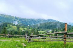 drewniany ogrodzenie w tle wioska w górach mgłowy fotografia stock