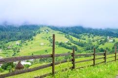 drewniany ogrodzenie w tle wioska w górach mgłowy zdjęcia royalty free