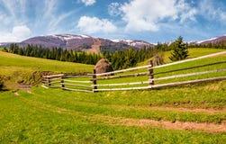 Drewniany ogrodzenie wzdłuż drogi gruntowej na trawiastych wzgórzach Fotografia Stock