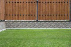 Drewniany ogrodzenie z kamienną podstawową i zieloną trawą w przodzie Obraz Stock