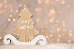 Drewniany ornament z tekstów Wesoło bożymi narodzeniami i złotym bokeh bożonarodzeniowe światła zdjęcie royalty free