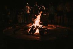 Drewniany palenie w ogniska nocnych ludziach w tle zdjęcie royalty free