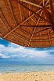 Drewniany parasol na białej piasek plaży obraz stock