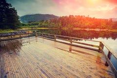 Drewniany pokład na a lakeshore Skalisty brzeg halny jezioro obrazy royalty free