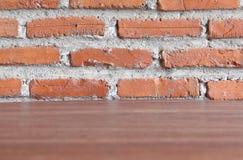 Drewniany pokładu stół z czerwonym ściana z cegieł Obraz Royalty Free