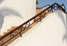 Drewniany poręcz z metalu wystrojem, elementem, szczegółem schody przeciw tłu cegła kroki i białą ścianą, obrazy royalty free