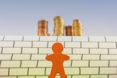 Drewniany postać stojak przed nieprzezwyciężoną ścianą z duży pieniądze wierza za zdjęcia royalty free