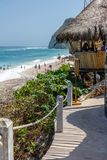 Drewniany przejście plażowy bar z pokrywającym strzechą dachem Ocean i ludzie na plaży na tle zdjęcia stock