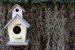 Drewniany ptaka dom na suchej trawy i zieleń liścia tle Obraz Stock