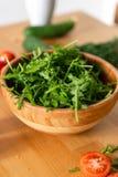 Drewniany puchar świeża zieleń, naturalny arugula z czerwonymi pomidorami na drewnianym tle Zdjęcia Royalty Free