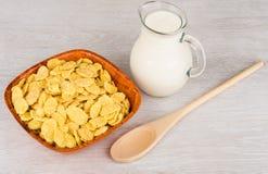 Drewniany puchar z kukurydzanymi płatkami, dzbankiem mleko i łyżką, Zdjęcie Royalty Free