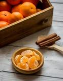 Drewniany pudełko z dojrzałym mandarynka cytrusem i cynamonowymi kijami fotografia royalty free