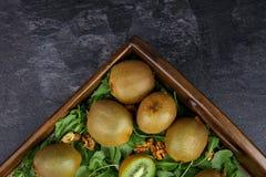 Drewniany pudełko z soczystymi kiwi w kamieniarza słoju na zmroku - szary tło, odgórny widok Kiwi na drewnianej tacy kosmos kopii Fotografia Royalty Free